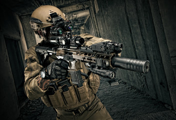 Special Forces operator in full gear with rifle, aiming at the enemy.
