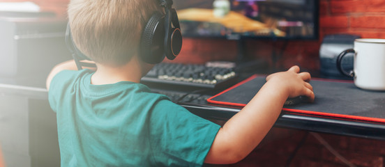 little boy playing games on computer in headphones with microphone, computer game