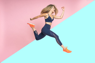 Beautiful young blond hair athlete woman is running and smiling jumping in the air in motion dressed in sportswear in two colors isolated background