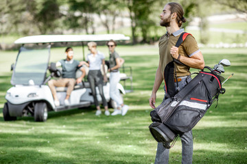 Handsome man standing with golf bag full of putters ready to play golf on the playing course with friends on the background