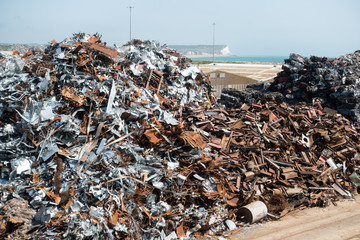 A large pile of scrap metal awaits shipment on a dock side jetty. White cliffs of West Sussex are visible on distant horizon- Image