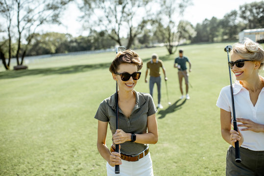 Two female best friends walking together with playing putters during a golf game on a course on a sunny day