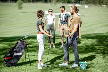 Young elegant friends meeting on the golf course before the play, having fun together on a sunny day