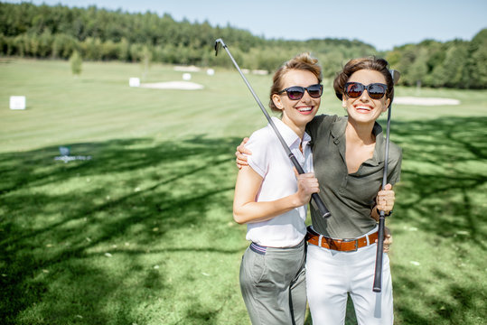 Portrait of a two female best friends standing with golf equipment on a playing course, talking and having fun during a game on a sunny day
