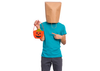 Fototapete - Happy halloween concept. Teen boy with paper bag over his head holds orange pumpkin bucket, isolated on white background. Portrait of teenager cover head with bag. Child waiting candy.