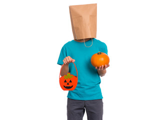 Fototapete - Happy halloween concept. Teen boy with paper bag over his head holds orange pumpkin bucket and small pumpkin, isolated on white background. Teenager cover head with bag. Child waiting candy.