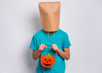Fototapete - Happy halloween concept. Teen boy with paper bag over his head holds orange pumpkin bucket, on grey background in studio. Portrait of teenager cover head with bag. Child waiting candy.