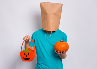 Fototapete - Happy halloween concept. Teen boy with paper bag over his head holds orange pumpkin bucket and small pumpkin, on grey background in studio. Teenager cover head with bag. Child waiting candy.