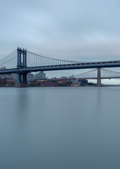 Brooklyn and Manhattan Bridges from East river on a cloudy morning with long exposure