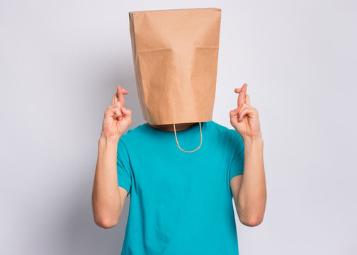 Portrait of teen boy with paper bag over head crossing his fingers and wishing for good luck. Teenager cover head with bag praying with crossed fingers posing in studio. Child pulling bag over head.