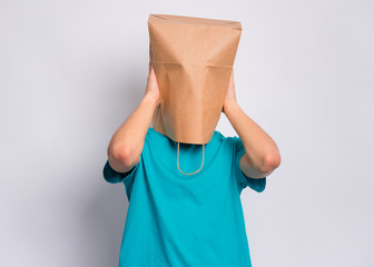 Fototapete - Portrait of teen boy with paper bag over head covering ears with his hands. Teenager cover head with bag closing ears with palms posing in studio. Child pulling bag over head. Hear no evil concept.