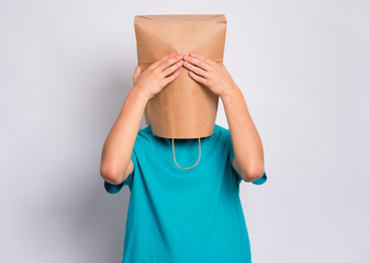 Fototapete - Portrait of teen boy with paper bag over head with hands on face covering eyes. Teenager cover head with bag close eyes with palms posing in studio. Child pulling bag over head. See no evil concept.