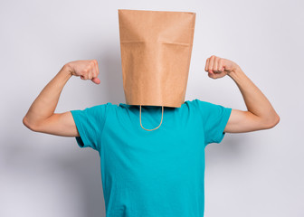 Fototapete - Portrait of teen boy with paper bag over head raised his hands and shows biceps. Teenager cover head with bag shows biceps posing in studio. Child pulling paper bag over head.