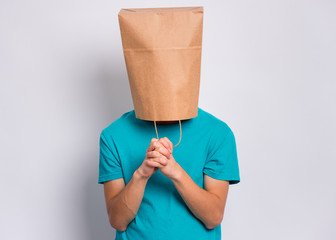 Fototapete - Teen boy with paper bag over head praying. Teenager cover head with bag with hands folded in prayer hoping for better posing in studio. Child asking God for good luck, success or forgiveness.