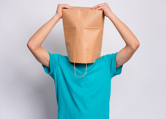 Fototapete - Portrait of surprised teen boy hold hands on head with paper bag over head. Teenager cover head with shopping bag, isolated on white background. Child with bag posing in studio.