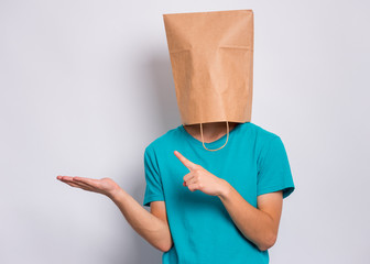 Fototapete - Teen boy with paper bag over head pointing finger away at copyspace, isolated on white background. Teenager cover head with shopping bag pointing finger at something. Child pulling paper bag over head