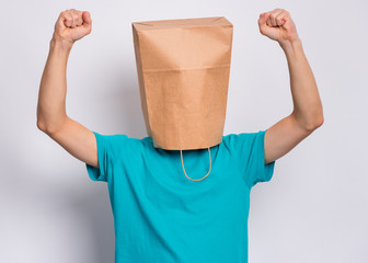 Fototapete - Portrait of teen boy with paper bag over head showing winning gesture. Successful and celebrating victory, triumphant child making win sign. Teenager cover head with bag, isolated on white background