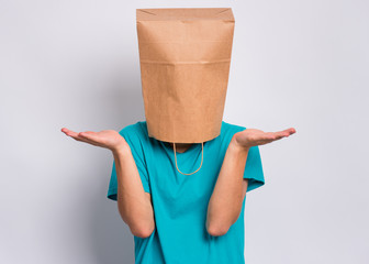 Fototapete - Portrait of teen boy with paper bag over head showing helpless gesture with hands - I do not know. Teenager cover head with bag, isolated on white background. Child making helpless sign.
