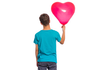 Fototapete - Back view. Portrait of teen boy holds red heart shaped balloon, isolated on white background. Child in blue t-shirt holding symbol of love, family, hope - rear view. Valentines Day concept.