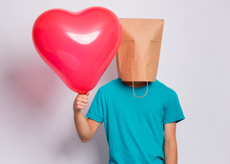 Fototapete - Valentines Day concept. Teen boy with paper bag over head holds red heart shaped balloon. Boy holding symbol of love, family, hope. Teenager cover head with bag posing in studio.