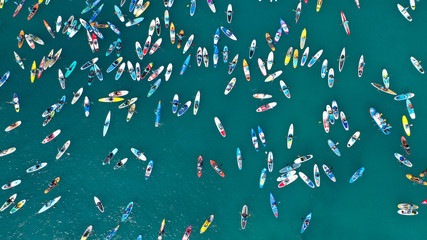 Aerial bird's eye view photo taken by drone of stand up paddle surfers in annual SUP crossing competition in Corinth Canal, Greece