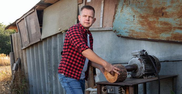 A man stabs a log with a splitter