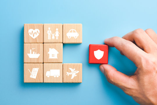 Hand holding red wooden blocks with insurance icons. family, life, car, travel, health and house insurance icons, blue background, Insurance concept