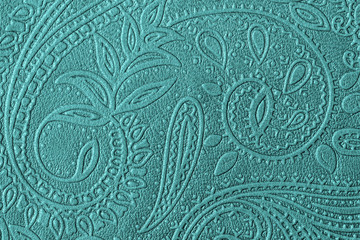 Texture of genuine leather with embossed floral trend pattern close-up, green mint color, for wallpaper or banner design. For modern background