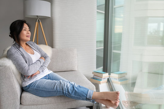 Mature Asian woman relaxing at home sitting on sofa chair enjoying view from condo apartment window thinking on weekend. Chinese lady in her 50s healthy life, early retirement relax concept.