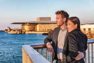 Wall Mural - Europe travel tourists couple enjoying sunset view at Copenhagen harbourfront by the Opera, Denmark european holiday lifestyle. Asian woman, Danish man interracial people.