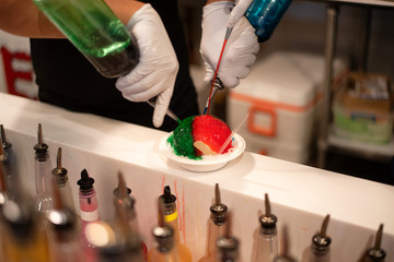 The making of a snow cone or shave ice bowl with different flavored colorful syrups