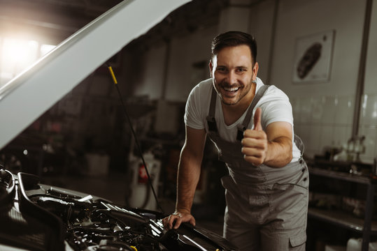 Happy mechanic showing thumbs up while working on a car in auto repair shop.He is looking at camera