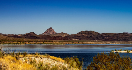 Alamo Lake State Park with purple mountains yellow grass and green flora in Arizona