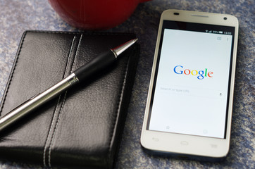 QUITO, ECUADOR - AUGUST 3, 2015: White smartphone lying on table with Google website screen open next to a pen, notepad and coffee mug, business communication concept