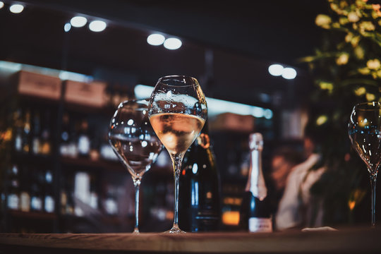 Wine glasses on the bar table, one glass is empty, but the second one is filled with white wine.