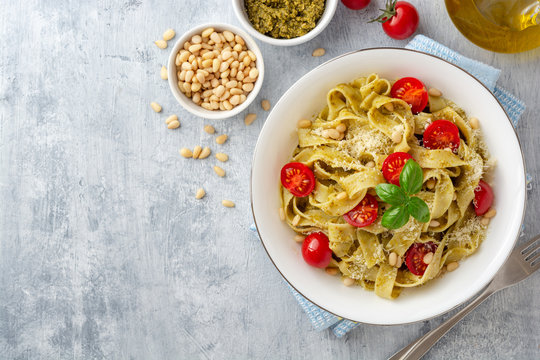 Fettuccine pasta with sauce pesto, cherry tomatoes, pine nuts and parmesan cheese on concrete background. Top view. Copy space.