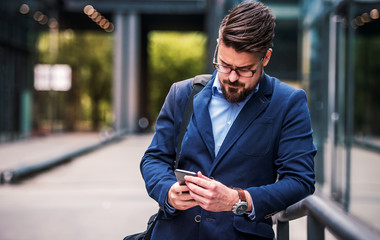 Business man standing in front of the office and using mobile phone. Business, education, lifestyle concept