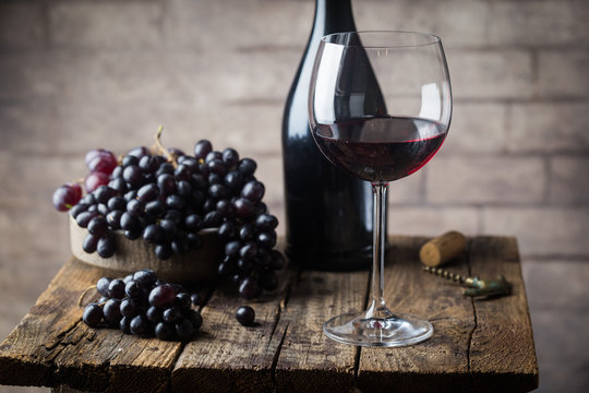 Red wine in a glass and ripe grapes on wooden table