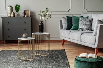 Two stylish small coffee tables with marble tops in front of elegant grey couch with emerald pillows Wall mural
