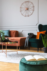 Velvet emerald green armchair with orange pillow next to corner sofa and coffee table