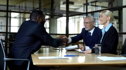 Happy black man and company boss shaking hands, successful interview, career