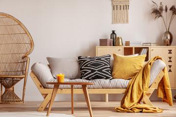 Stunning wicker peacock chair next to modern scandinavian settee with pillows