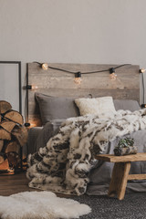 Copy space on empty grey wall of warm bedroom with winter design