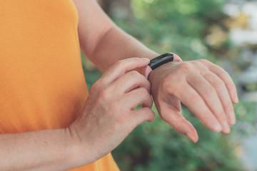 Female hiker using smart wristband during trekking in nature