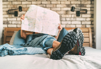 Fotobehang - Young female inspecting a city map resting on the bed under the blanket weared trekking boots on bed sheets. Boot sole close up shot.