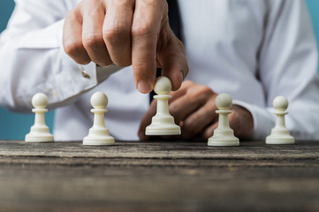 Businessman positioning white pawn chess piece in front of the others