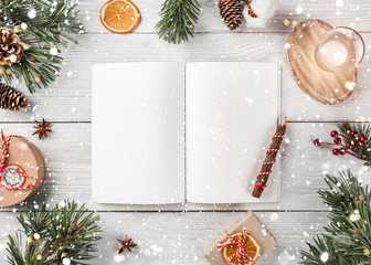 Fototapete - Creative layout made of Christmas tree branches with holiday book, pencil, pine cones, gifts on white background. Xmas and Happy New Year theme, bokeh, sparking, glowing. Flat lay, top view