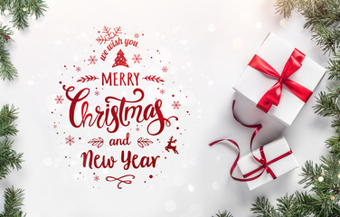 Fototapete - Merry Christmas text on white background with gift boxes, fir branches, red decoration. Xmas and New Year greeting card, bokeh, light. Flat lay, top view, winter holiday