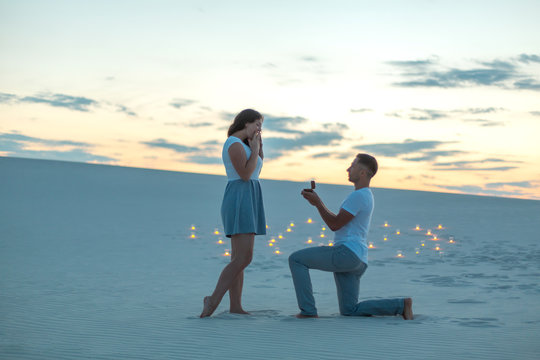 The guy makes the girl a marriage proposal by bending his knee while standing on the sand in the desert. Evening, candles burn in the sand.