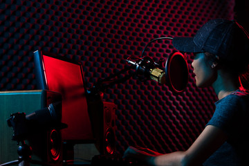 Young Adult sing a cover Song on Youtube. Woman connect social media with professional equipment such as e-sport gaming keyboard, mouse, monitor, speaker, camera, studio, dark red blue theme